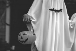 kid dressed as ghost with pumpkin
